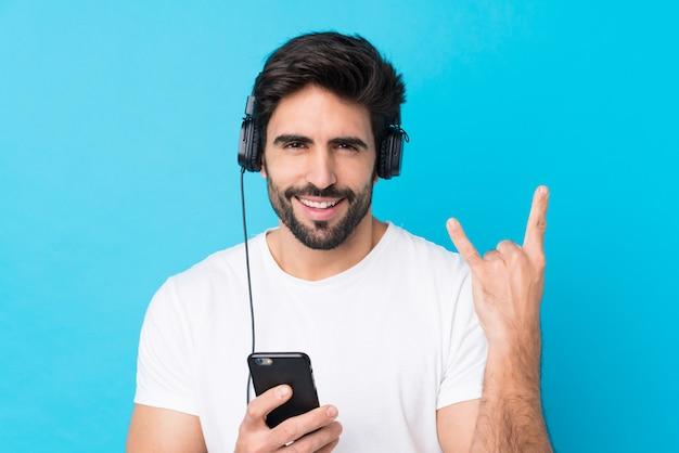 Giovane uomo bello con la barba sopra musica d'ascolto isolata della parete blu con un gesto di fabbricazione mobile della roccia