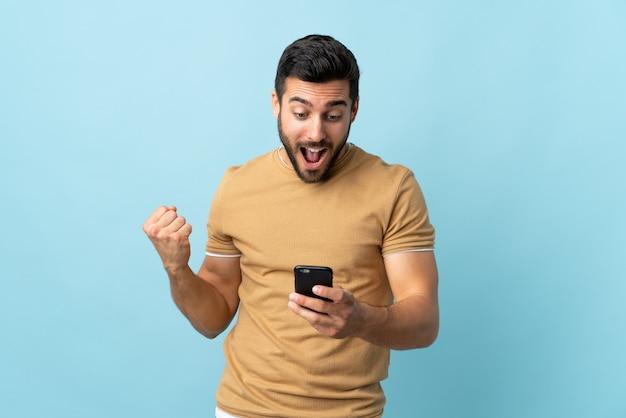 Giovane uomo bello con la barba sorpreso e l'invio di un messaggio