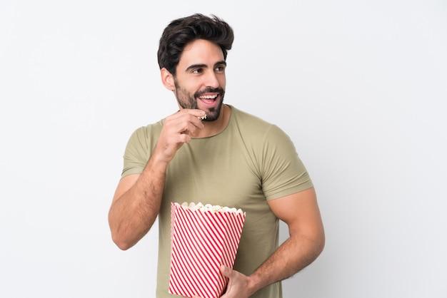 Giovane uomo bello con la barba sul muro bianco isolato in possesso di un grande secchio di popcorn