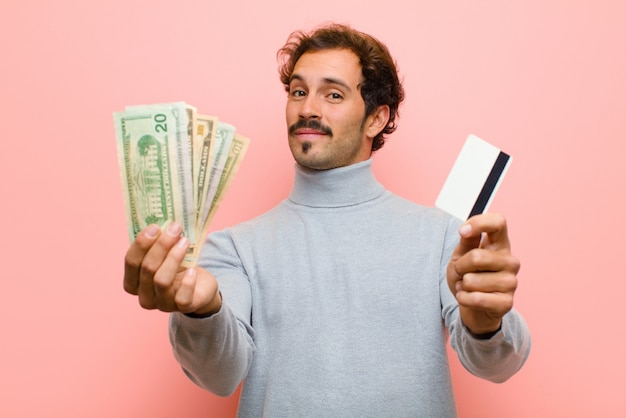 Giovane uomo bello con le banconote del dollaro contro la parete piana rosa