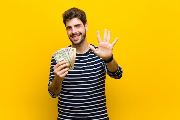 Giovane uomo bello con le banconote del dollaro
