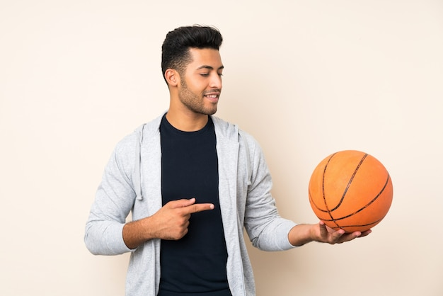 Giovane uomo bello con palla di basket e puntandolo