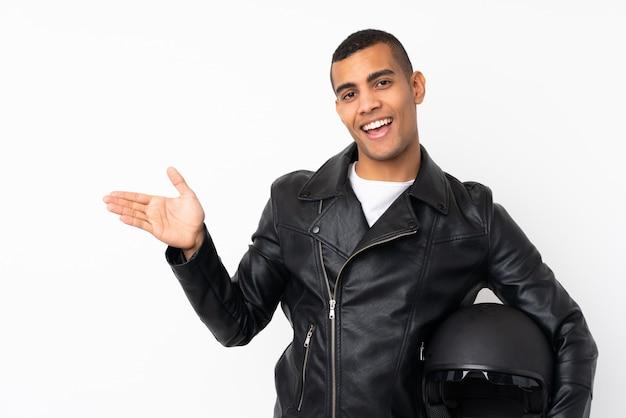 Giovane uomo bello con un casco da motociclista sul muro bianco isolato che estende le mani a lato per invitare a venire
