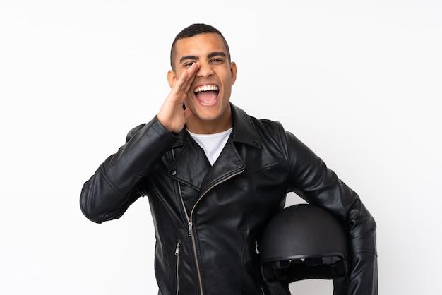 Giovane uomo bello con un casco del motociclo sopra la parete bianca isolata che grida con la bocca spalancata
