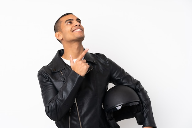 Giovane uomo bello con un casco del motociclo sopra la parete bianca isolata che indica con il dito indice una grande idea