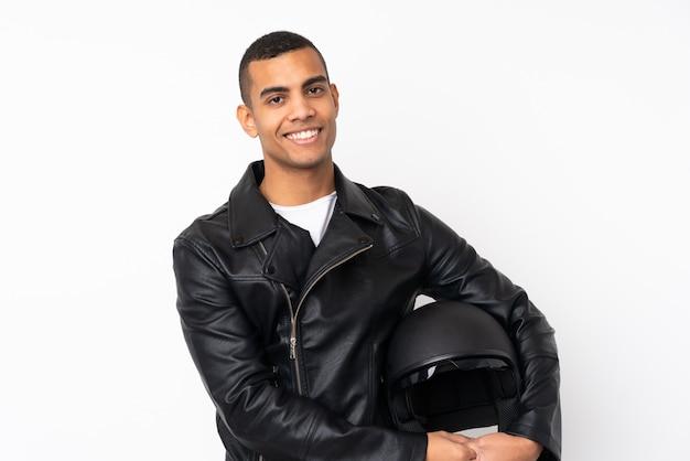 Giovane uomo bello con un casco del motociclo sopra la risata bianca isolata della parete