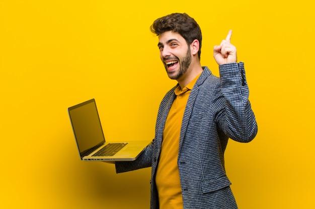 Giovane uomo bello con un computer portatile su sfondo arancione