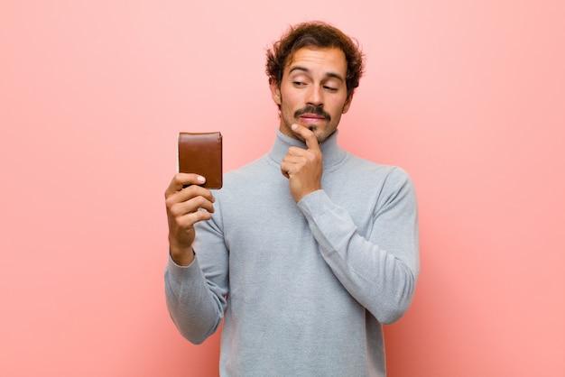 Giovane uomo bello con un portafoglio contro la parete piana rosa