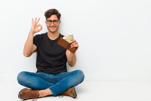 Giovane uomo bello con un portafoglio seduto sul pavimento, seduta sul pavimento in una stanza bianca
