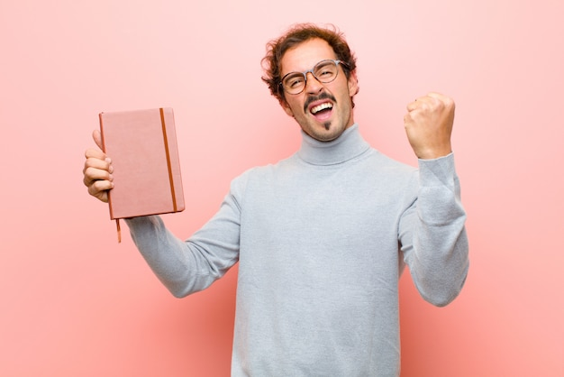 Giovane uomo bello con un taccuino contro la parete piana rosa
