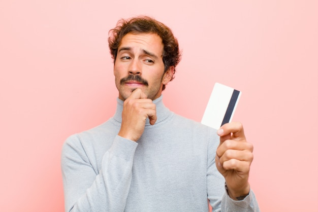 Giovane uomo bello con una carta di credito contro la parete piana rosa