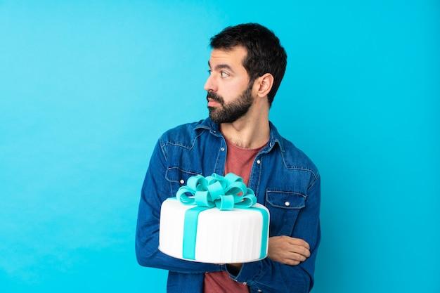 Giovane uomo bello con una grande torta sopra il ritratto blu isolato della parete