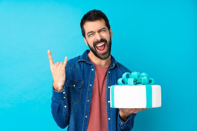 Giovane uomo bello con una grande torta sopra la parete blu isolata che fa gesto di roccia