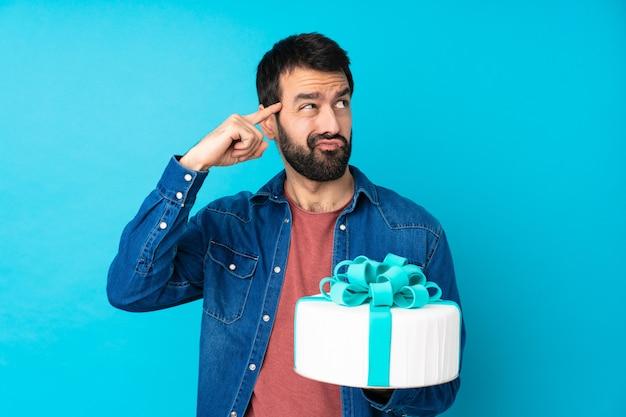 Giovane uomo bello con una grande torta sopra la parete blu isolata che fa il gesto della follia che mette il dito sulla testa