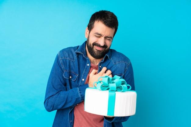 Giovane uomo bello con una grande torta sopra la parete blu isolata che ha un dolore nel cuore