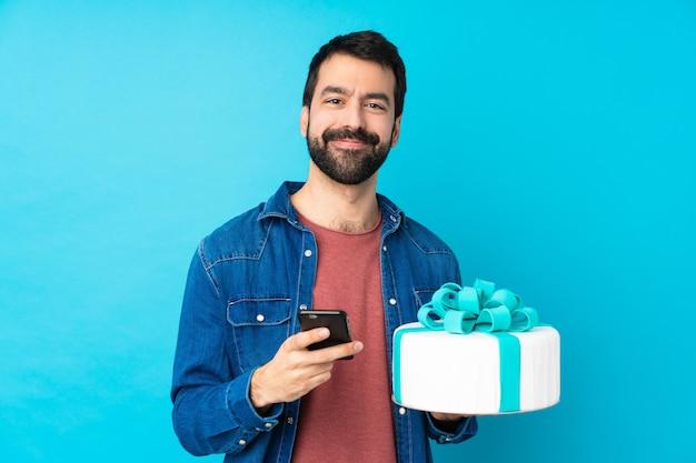 Giovane uomo bello con una grande torta sopra la parete blu isolata che invia un messaggio con il cellulare