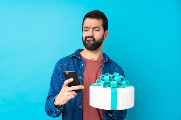 Giovane uomo bello con una grande torta sopra la parete blu isolata che pensa e che invia un messaggio