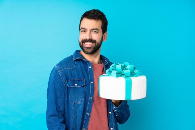 Giovane uomo bello con una grande torta sopra la risata blu isolata della parete