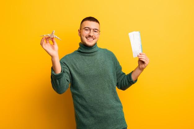 Giovane uomo bello contro la parete piana con i biglietti della carta d'imbarco