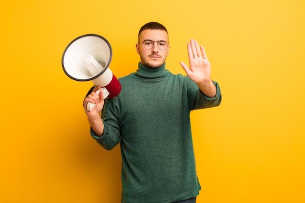 Giovane uomo bello contro la parete piana con un megafono
