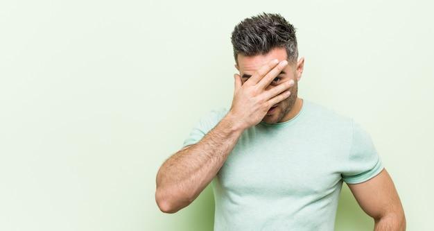 Giovane uomo bello contro un battito di ciglia verde alla macchina fotografica attraverso le dita, volto di copertura imbarazzato.