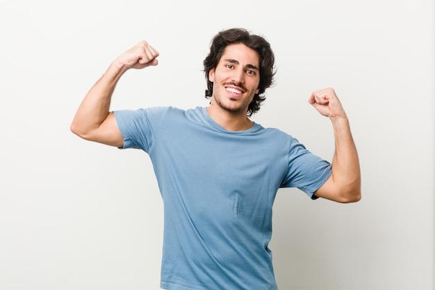 Giovane uomo bello contro un muro bianco che mostra il gesto di forza con le braccia, simbolo del potere femminile