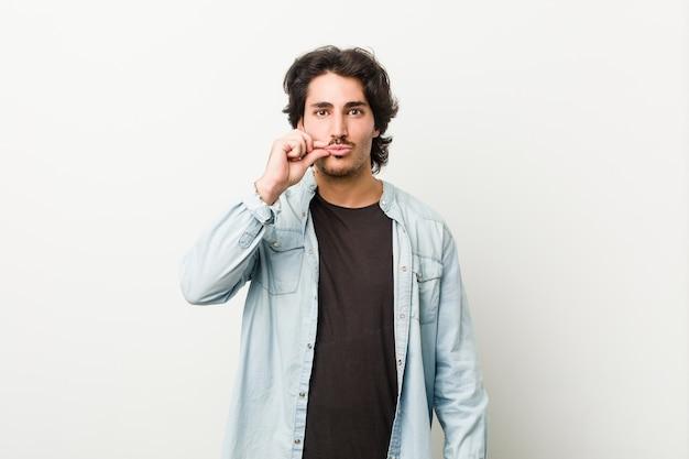 Giovane uomo bello contro un muro bianco con le dita sulle labbra mantenendo un segreto.
