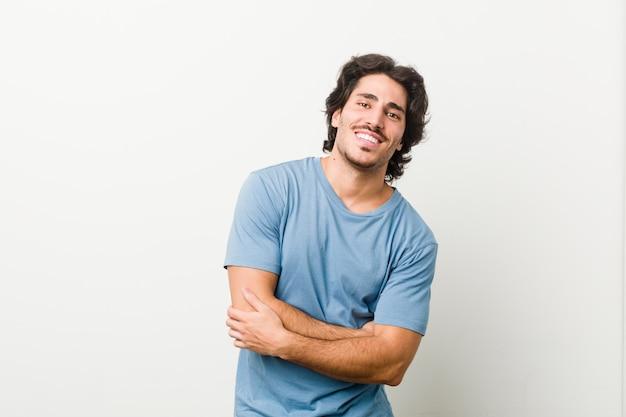 Giovane uomo bello contro un muro bianco ridere e divertirsi.