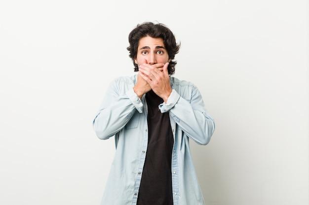 Giovane uomo bello contro un muro bianco scioccato che copre la bocca con le mani.
