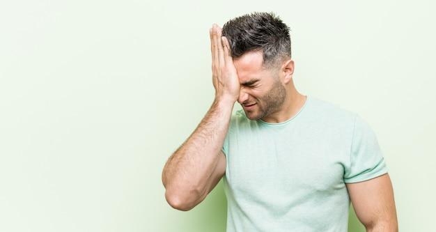 Giovane uomo bello contro un verde che dimentica qualcosa, schiaffeggiando la fronte con il palmo e chiudendo gli occhi.