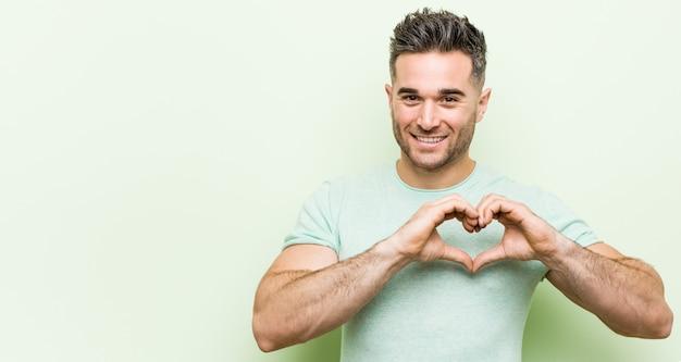 Giovane uomo bello contro un verde che sorride e che mostra una forma di cuore con le mani.