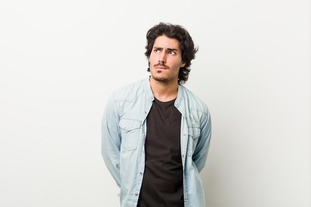 Giovane uomo bello contro uno sfondo bianco confuso, si sente dubbioso e incerto.