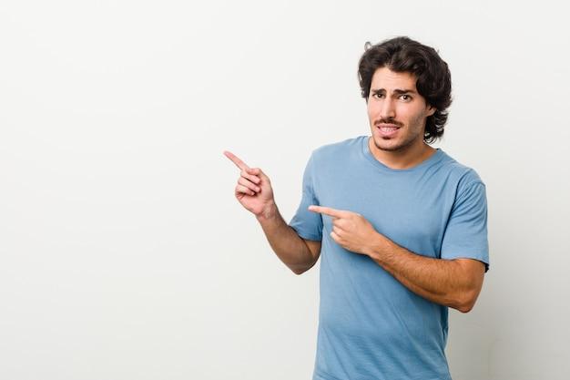 Giovane uomo bello contro uno sfondo bianco scioccato indicando con il dito indice uno spazio di copia.
