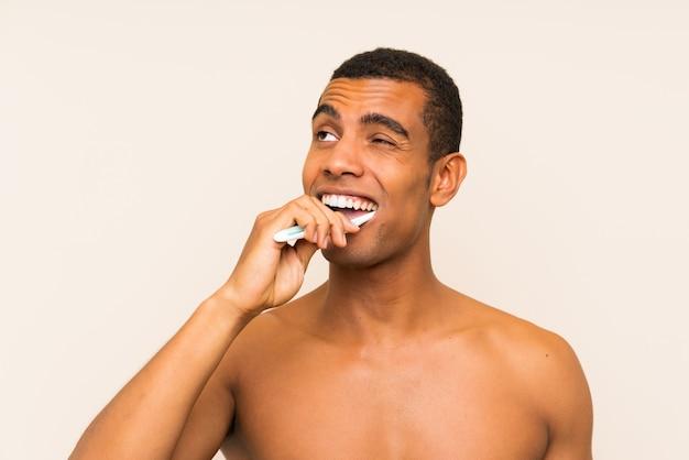 Giovane uomo bello del brunette che pulisce i suoi denti