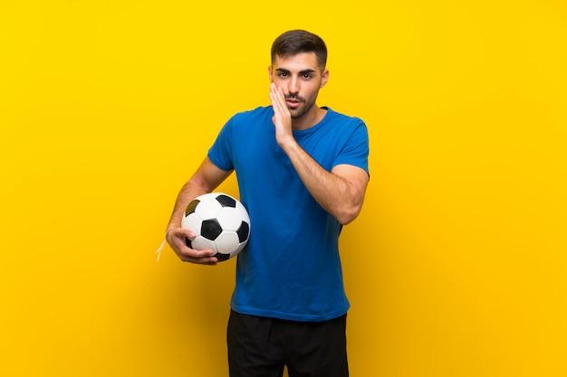 Giovane uomo bello del giocatore di football americano sopra la parete gialla isolata che bisbiglia qualcosa