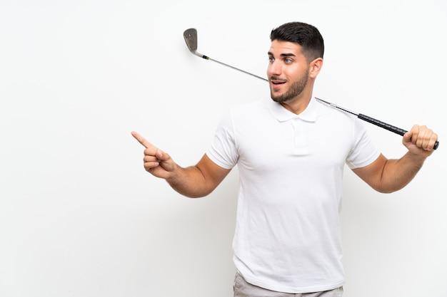 Giovane uomo bello del giocatore di giocatore di golf sopra la parete bianca isolata sorpresa e indicando dito il lato