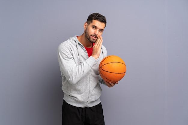 Giovane uomo bello del giocatore di pallacanestro che bisbiglia qualcosa