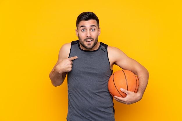 Giovane uomo bello del giocatore di pallacanestro sopra la parete bianca isolata con espressione facciale di sorpresa