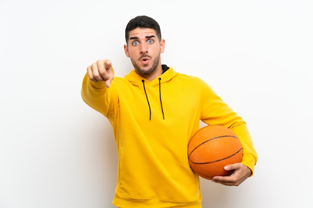 Giovane uomo bello del giocatore di pallacanestro sulla parete bianca sorpresa e indicante parte anteriore
