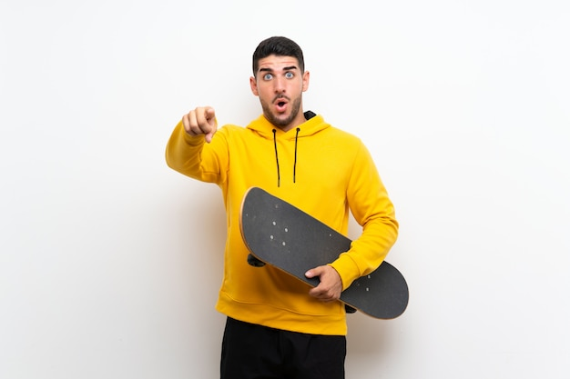 Giovane uomo bello del pattinatore sopra la parete bianca isolata sorpresa e indicando parte anteriore