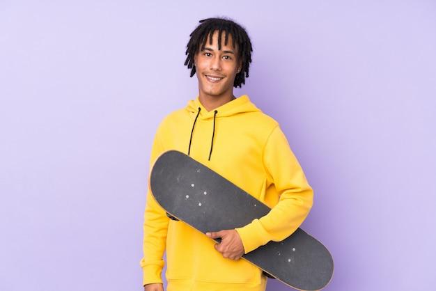 Giovane uomo bello del pattinatore sopra la parete isolata che sorride molto