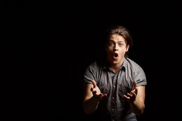 Giovane uomo bello deludente che gesturing, gridando