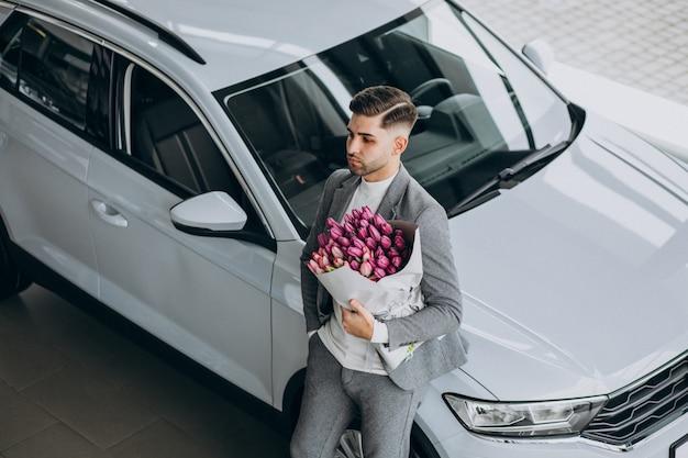 Giovane uomo bello di affari che consegna mazzo di bei fiori