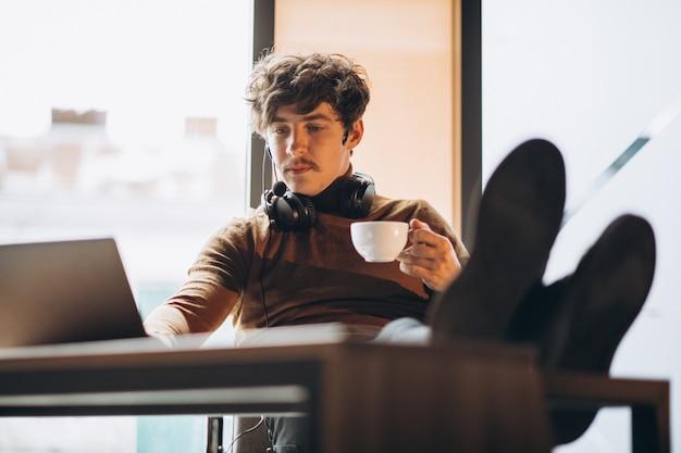 Giovane uomo bello di affari che lavora al computer e che beve caffè