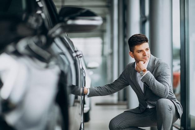 Giovane uomo bello di affari che sceglie un'automobile in una sala d'esposizione dell'automobile
