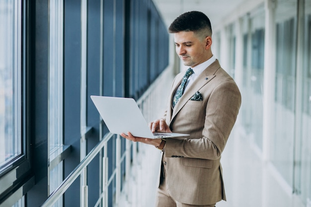 Giovane uomo bello di affari che sta con il computer portatile all'ufficio