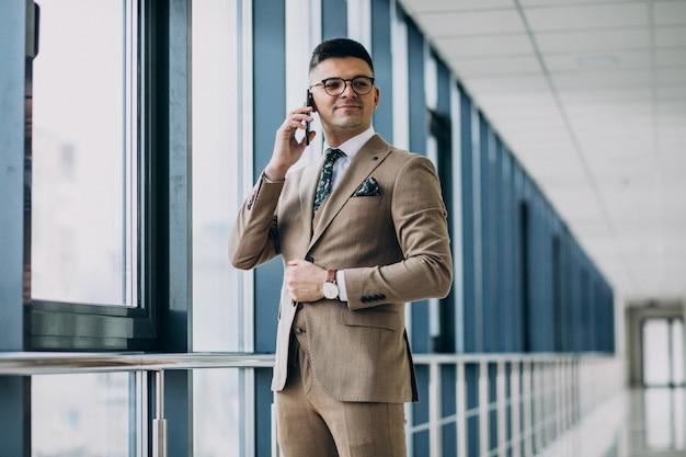 Giovane uomo bello di affari che sta con il telefono all'ufficio