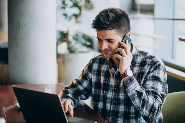Giovane uomo bello di affari che utilizza computer portatile in un caffè