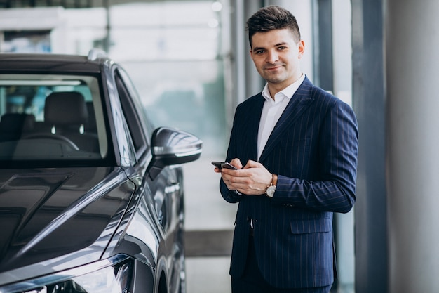 Giovane uomo bello di affari in una sala d'esposizione dell'automobile che sceglie un'automobile