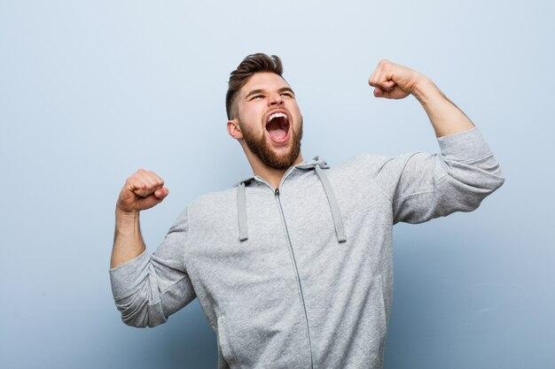 Giovane uomo bello di forma fisica che alza pugno dopo una vittoria, concetto del vincitore.